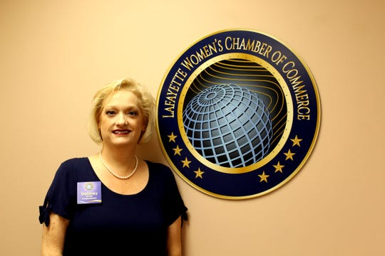 Debbey Ryan, founder and president of the Lafayette Women's Chamber of Commerce, stands next to the logo at the organization's headquarters.