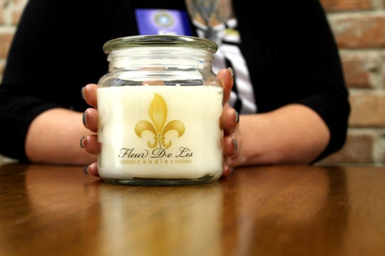 Kim Price, owner of Fleur de Lis Candles, holds her product at the Lafayette Women's Chamber of Commerce headquarters.