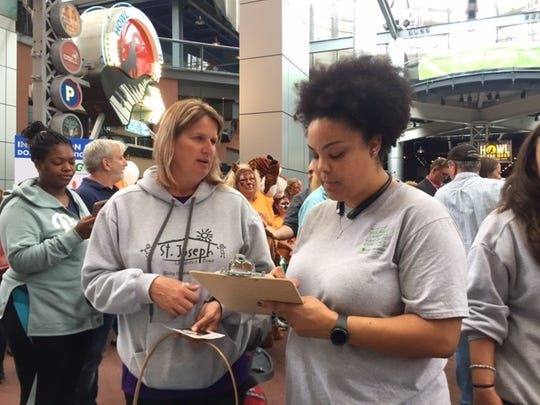 Former Prichard Committee staff member Alana Morton conducts an education survey on Fourth Street in Louisville during a community rally.