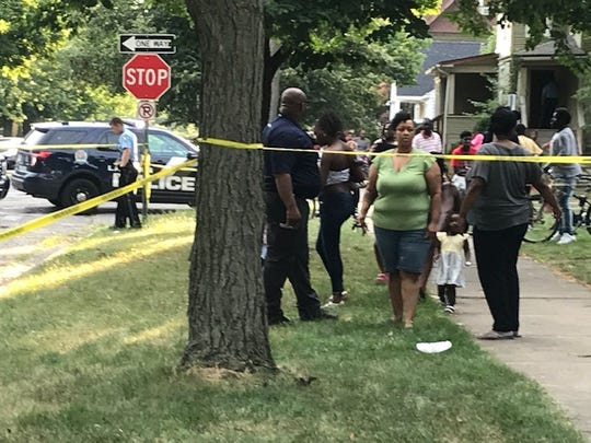 Spectators gathered at the scene of a shooting that left one person dead and two others injured Monday , Aug. 5, 2019 near downtown Lansing.