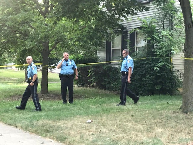 Lansing police officers work at the scene of a shooting on West Genesee Street on Monday, Aug. 5, 2019.