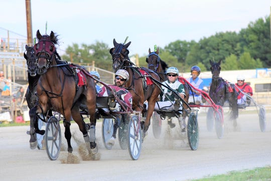 A group of drivers speed into the second lap of their harness race Monday evening during the Richland County Fair.