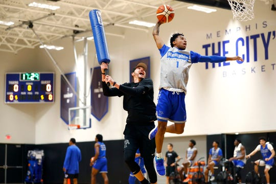 Memphis guard Tyler Harris dunks past the defense of assistant coach Mike Miller during practice Tuesday at the Laurie-Walton Family Basketball Center.