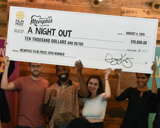 "Cinematographer Andrew Trent Fleming (left), co-directors Kevin Brooks and Abby Meyers and actress Rosalyn Ross hoist a prop prize check at Aldo's after winning the 2019 Memphis Film Prize with their short film ""A Night Out."""
