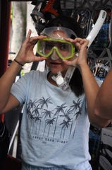 Danielle Donatelli tries on a mask in the dive shop. Scuba Marco offers divers the chance to experience scuba diving at reefs and wrecks right off the island's shores.