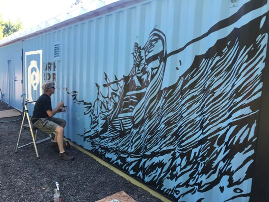 Artist Greg Wimmer paints a mural based on labels from Earth Rider Brewery on the side of the Tin Tap House outside Delta Diner in Wisconsin.
