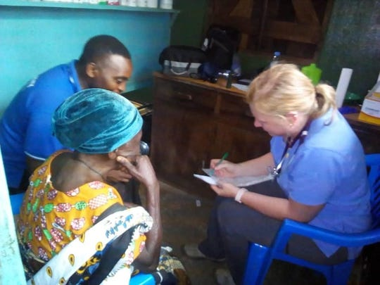 Nicki Pantuso, a registered nurse and Wauwatosa resident, asks patients questions in a clinic in Tanzania. Pantuso was a part of a mission trip to provide medical services.