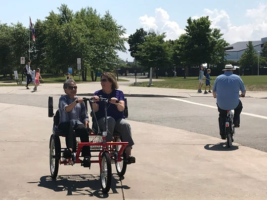 Shirin Cabraal of Disability Rights Wisconsin and Deb Falk-Palec, chair of the Milwaukee County Commission for Persons with Disabilities, try out one of the new adaptive bikes that are part of the Bublr bike share program Tuesday at Discovery World.