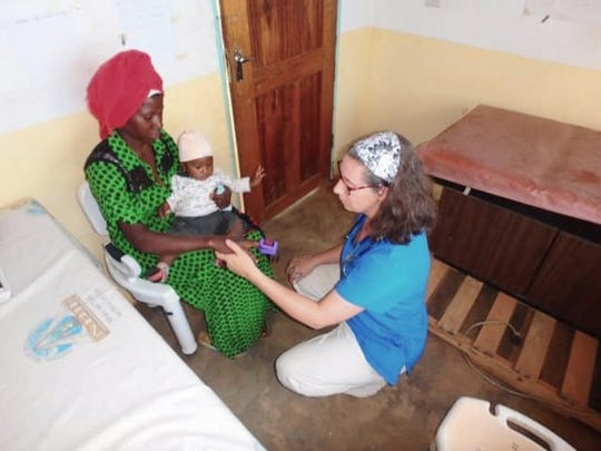 Nicole Gerboth, a Wisconsin registered nurse, assists a patient and baby at a clinic in Tanzania in July. Gerboth was a part of the Salvatorian Mission Warehouse trip to provide medical services.