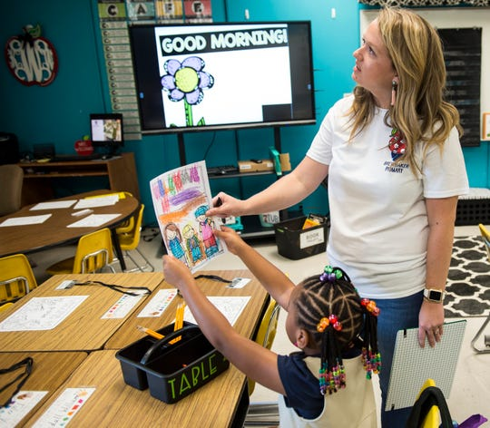 First grade teacher Katlyn Williams checks out one of her students drawings during the first day of school at Brewbaker Primary School in Montgomery, Ala., on Tuesday, Aug. 6, 2019.