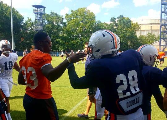 Auburn linebacker K.J. Britt (33) high-fives running back JaTarvious Whitlow (28) during practice on Aug. 6, 2019, in Auburn, Ala.