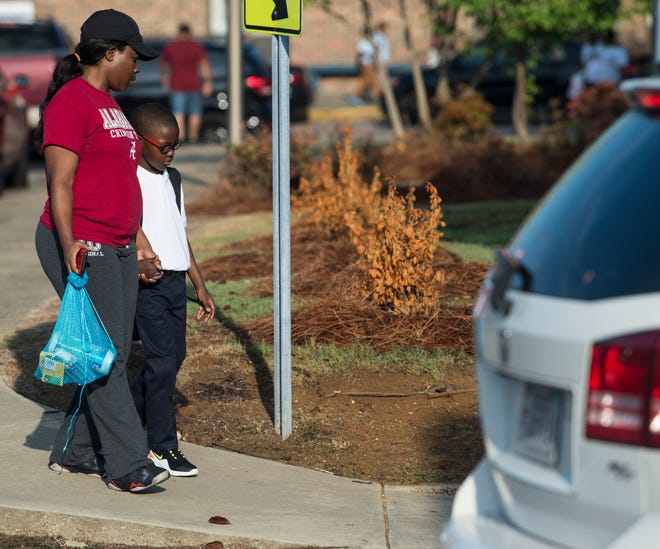 Terrisha Standberry and her son, Tyler Watkins, 7, walk into school for Tyler's first day of second grade at Brewbaker Primary School in Montgomery, Ala., on Tuesday, Aug. 6, 2019.