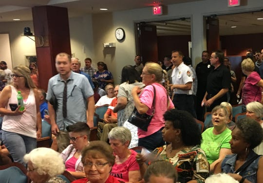 The crowd is stunned after city council President Doug Marshall abruptly ended   citizen comments at a meeting Monday night.