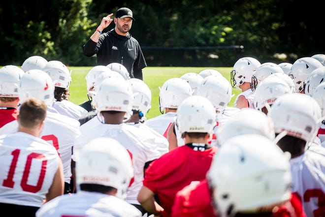 FILE -- Ball State football coach Mike Neu speaks with his players after a previous fall camp practice. The first phase of BSU Athletics' phased return is a group of football players who can come to campus for voluntary workouts.