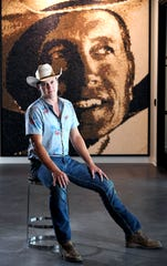 Jon Pardi sits in front of a George Strait photograph at Universal Music Group Nashville on Aug. 6, 2019. When Pardi was young, he told his preschool teacher that his name was George Strait.