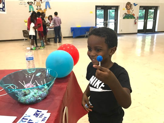 Isaiah Black, a Kindergarten student, is happy with a sucker he was given by the Parent Teacher Organization booth at the Liberty Elementary meet and greet Monday.