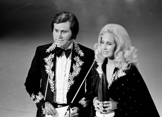 "George Jones and Tammy Wynette got divorced, but that didn't stop them from continuing to release hit duets, including ""Golden Ring,"" in 1975. Here, they get ready to announce the Album of the Year winner at the eighth annual CMA Awards show Oct. 14, 1974."