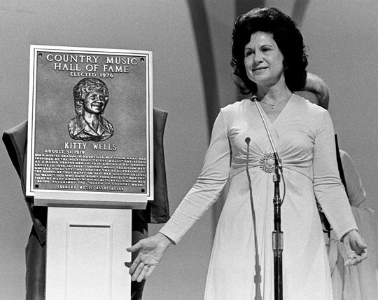 "With ""It Wasn't God Who Made Honky Tonk Angels,"" Kitty Wells became the first female solo artist to top Billboard's country chart in 1952. Here, Wells, known as the Queen of Country Music, gives thanks after her induction into the Country Music Hall of Fame by Minnie Pearl, last year's inductee, at the CMA Awards show at the Grand Ole Opry House on Oct. 11, 1976."