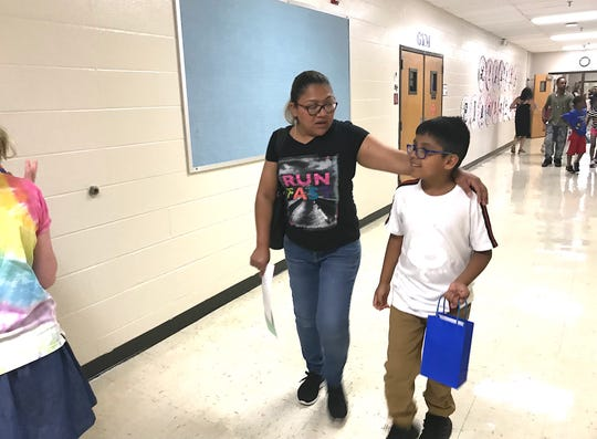 Mom Guadalupe Nava puts her arm around her son, Alex Ortiz, as the two visit his new classroom and meet his new teacher before school starts this week.