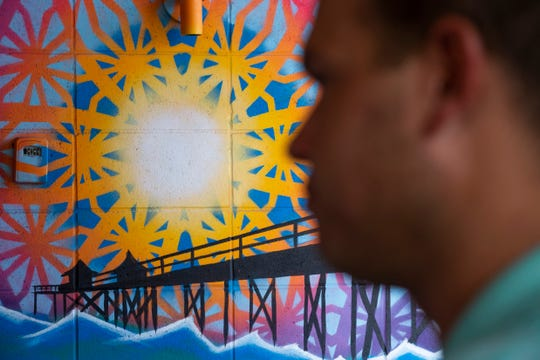 Patrick Johnson, the general manager of Celebration Park Naples, stands in front of a mural featuring the Naples Pier on Tuesday, August 6, 2019, in East Naples.
