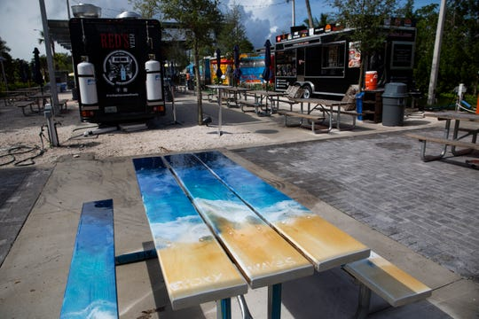 A farmhouse table painted with ocean waves sits in the Celebration Park on Tuesday, August 6, 2019, in East Naples.