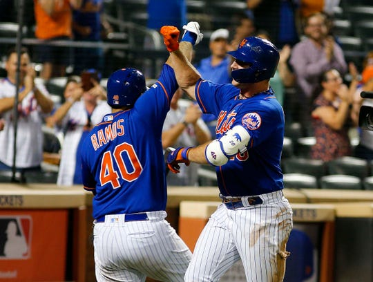 New York Mets first baseman Pete Alonso (20) is congratulated by catcher Wilson Ramos (40) after hitting a solo home run against the Miami Marlins during the seventh inning of game two of a doubleheader at Citi Field.