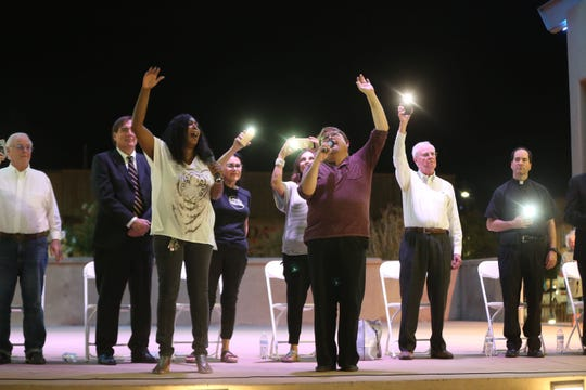 Bobbie Green, left, and Orlando-Antonio Carillo-Jiménez, right, lead the crowd in song at a solidarity event Monday at Plaza de Las Cruces. Members of the Las Cruces City Council are also on stage.