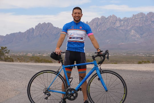 Nathan Espinosa stands with his bicycle in front of the Organ Mountains.