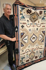 Appraiser Jackson Clark displays a large Teec Nos Pos rug that features various pictorial elements Aug. 6 at the Farmington Museum at Gateway Park.