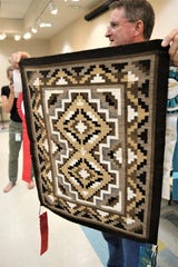Farmington Museum director Bart Wilsey displays a donated Two Grey Hills weaving Aug. 6 at the museum.