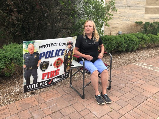 Margie Runyan, a retired Bloomfield Township dispatcher, sits outside of Brother Rice High School on Tuesday, urging voters to support the S.A.D. proposal.