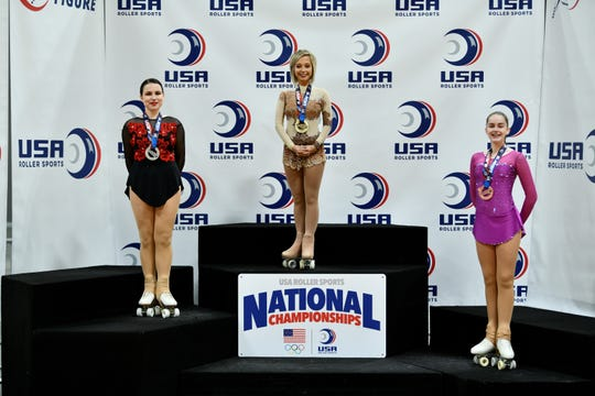 Livonia's Amanda Smyser (center) stands on the podium after winning a gold medal at the USA Roller Skating national competition in Spokane, Washington in July 2019.
