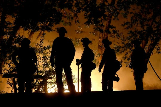 CALISTOGA, CA - OCTOBER 12:   CalFire firefighters monitor a firing operation as they battle the Tubbs Fire on October 12, 2017 near Calistoga, California. At least thirty one people have died in wildfires that have burned tens of thousands of acres and destroyed over 3,500 homes and businesses in several Northen California counties.  (Photo by Justin Sullivan/Getty Images)