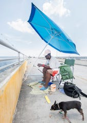 Beatrice Laster baits her line Tuesday as she and her Chihuahua, Smoke, fish off the old Pensacola Bay Fishing Bridge