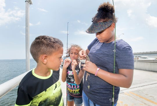 At left, Joseph Schuka, 9, looks on as his sister Samantha, 8, untangles their fishing line and Alyssia, 12, tries to unhook the fish that they just caught on the old Pensacola Bay Fishing Bridge.