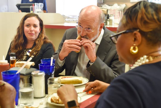 Pennsylvania Gov. Tom Wolf eats a hot dog at the Famous Hot Weiner in downtown Hanover on Tuesday, August 6, 2019. Main Street Hanover Executive Director Justine Trucksess (left) and Hanover Mayor Myneca Ojo (right) joined him.