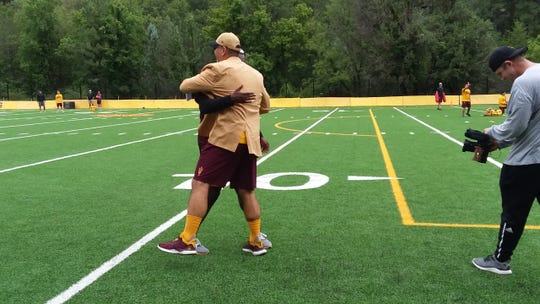 Offensive analyst Kevin Mawae embraces ASU football coach Herm Edwards at the first day of practice at Camp Tontozona in Payson on Monday.
