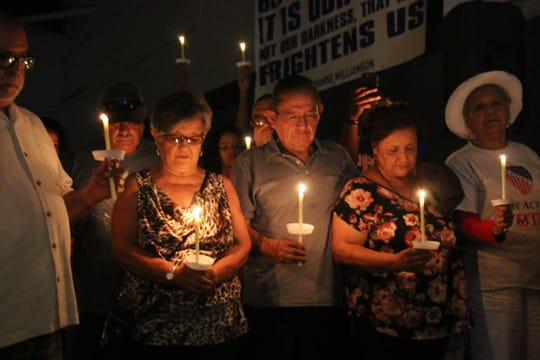 Community members listen to a prayer at a candlelight vigil in Phoenix for victims of the Dayton, Ohio and El Paso, Texas shootings.