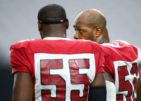 Cardinals linebackers Chandler Jones (55) and Terrell Suggs talk during a training camp practice Aug. 6 at State Farm Stadium.
