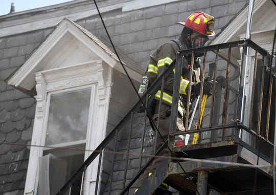 Firefighters use a fire escape to access the third floor of a multi-unit building at the corner of N. Queen Street and Chestnut Street, Tuesday, August 6, 2019.John A. Pavoncello photo
