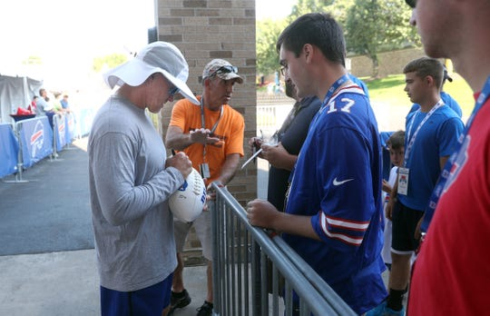 Head coach Sean McDermott stops to sign an autograph before practice.