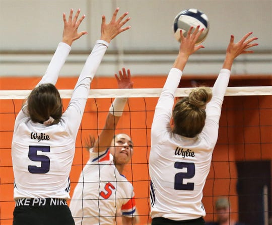 San Angelo Central's Mya Moore (background) tries to drive the ball past Abilene Wylie's Lilly Kate Doby (5) and Avery Wimberly during the volleyball season opener at Central's Trevino gym on Tuesday, Aug. 6, 2019.