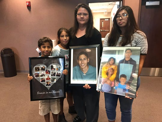 Kristi Renville, center, mother of Darias Tiger, and her children hold photos of Tiger at the sentencing of Stasek Stefanyuk Tuesday, Aug. 6, 2019. Stefanyuk was sentenced to 12 years in prison for Tiger's death.