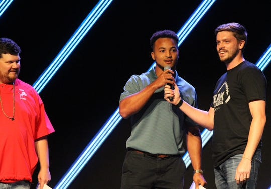 City Church youth director Zach Meredith holds the microphone as St. John Paul II assistant coach Isaiah Hill, a former Florida High star, introduces himself for trivia during the sixth-annual Team Tallahassee kick-off dinner at City Church on Aug. 5, 2019.