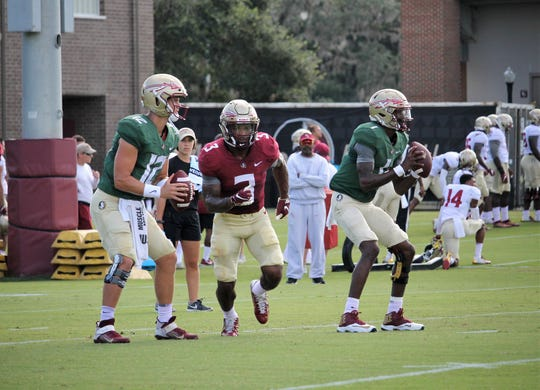 Quarterbacks Alex Hornibrook (left) and James Blackman (right) work on a drill will running back Cam Akers at FSU football practice on Aug. 6, 2019.