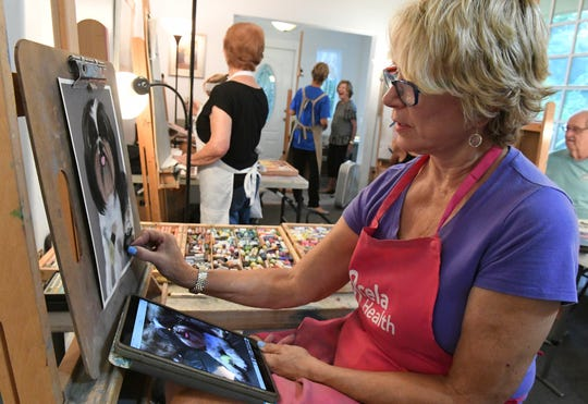 "Connie Zahorchak, of Port St. Lucie, works with chalk on a painting Tuesday, Aug. 6, 2019, during a studio class at the home of Dawn Miller (background in blue) in the 1900 block of 19th Avenue in the Edgewood neighborhood of Vero Beach. ""I've known Dawn for quite a few years, and I think she's the best teacher to critique what you do and I always learn something from her, and it's great camaraderie here, great place to be,"" Zahorchak said. The class brought together several artists to work together while working on their own projects. ""I think that Vero Beach is ready, and long past ready for a cultural arts village,"" Dawn Miller said."