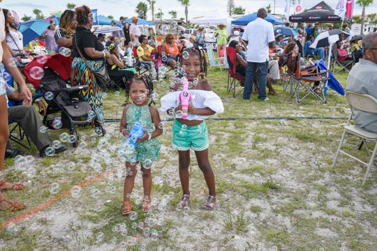 "Camryn and Chloe get a ""bubble bath"" at the Caribbean American Cultural Group's Jerk Festival at the Causeway Cove Marina in Fort Pierce."
