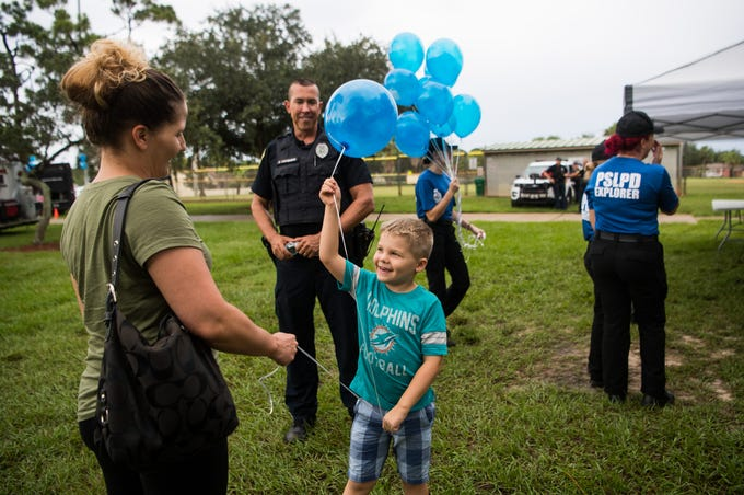 "Grayson Chalmers (center), 5, shows his mother, Rachel Chalmers, both of Port St. Lucie, the balloon he received from Port St. Lucie Police Department Officer Raphael Lushbaugh at Lyngate Park during National Night Out Against Crime on Tuesday, Aug. 6, 2019, in Port St. Lucie. PSLPD Chief John Bolduc said the goal of the evening was to get his officers out to mingle with the community. ""During this week, all over the country, people are getting out and doing this,"" he said. ""A few years ago we went to this multi-place in the city format where we can try and touch more people... with the weather today, we're actually talking about maybe we should do a 'national night in' next year,"" he added, remarking on the rainy day. The city's Downtown Trolley took PSLPD command staff members and City of Port St. Lucie government officials to various stops in Districts 1-4 throughout the evening as part of the event."