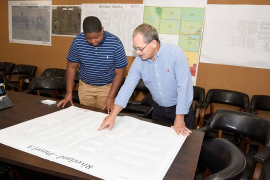 Boys & Girls Club member Justus Jones, left, and GL Homes Vice President Rick Elsner, a professional engineer, examine site plans for the Riverland residential development in Port St. Lucie.