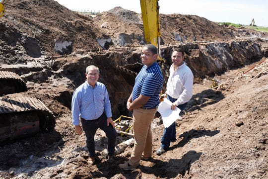 Boys & Girls Club member Justus Jones, center, with GL Homes Vice President Rick Elsner, left, and Director of Land Development Mike Fogarty out in the field at the company's Riverland development in Port St. Lucie.
